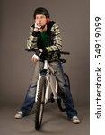 The bicyclist on gray background, studio shot. - stock photo