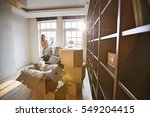 woman unpacking lamp from... | Shutterstock . vector #549204415