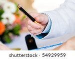 A groom holding a black and gold pen on his wedding day - stock photo