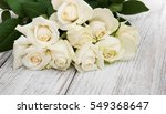 Stock photo white roses on a old white wooden table 549368647