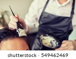 Small photo of beauty and people concept - close up of stylist with hair dye and brush coloring hair at salon