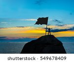 Small photo of High achiever, silhouette of a man hold in hand empty flag on top of a mountain. Man on top of mountain. Conceptual design. male against blue and yellow dramatic sky with clouds. hand's up.