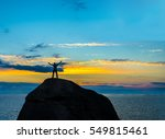Small photo of High achiever, silhouette of a man on top of a mountain. Man on top of mountain. Conceptual design. male against blue and yellow dramatic sky with clouds. hand's up.