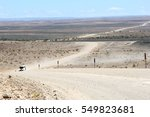 Small photo of Touring car drives on a dusty African gravel roads to Fish River Canyon in a desolate desert landscape, Namibia, Africa