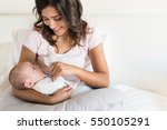 young mother with baby in bed | Shutterstock . vector #550105291