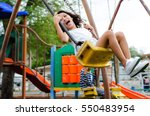 smiling girl playing on a swing | Shutterstock . vector #550483954