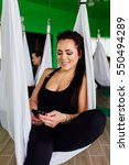 Small photo of young women Resting with smartphone after antigravity yoga exercises with a group of people. aero fly fitness trainer workout. white hammocks, eco green background studio. interior mirrors.