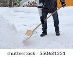 A Man Shovels Snow Of The...