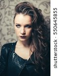 Small photo of Punk rock style or halloween make-up. Fashion woman model face with bright glamour makeup. Perfect skin, black gloss eyeshadows on eyes and dark brown glossy lips visage. Vintage colours.