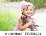 Stock photo beautiful little girl in a pink dress and pink headband holding gray kitten and smiling 550856101