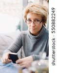 mid age woman with cell phone... | Shutterstock . vector #550882249