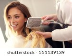 hairdresser using hair brush in ... | Shutterstock . vector #551139139