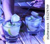 Small photo of A young girl is preparing an alcoholic or non-alcoholic cocktail. hands, bartender, bar, restaurant, mint, lime, lemon, alcoholic, non-alcoholic