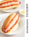 Small photo of Chilean Completo Clasico (classical) or Aleman (German) traditional hot dog sandwiches with tomato and sauerkraut, photographed with natural light (Selective Focus, Focus one third into first hotdog)