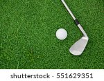 Stock photo top view of iron golf club and ball on a green grass 551629351