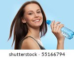 Beautiful girl drinking water from bottle on blue background - stock photo