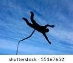 Silhouette of the rope-jumper against the sky - stock photo