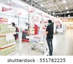 Small photo of Blurred abstract background Asian person waiting for paying products in a shopping cart at the row of cashier counter checkout in the Supermarket store: Blurry cashiers serves customers.