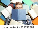 Stock photo funny young man lying on floor among books 551792284