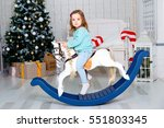 Girl On A Toy Horse Near A...