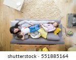 a mother is lying on the sofa... | Shutterstock . vector #551885164