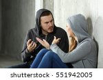Small photo of Couple of teenagers arguing sitting on the floor in a dark place