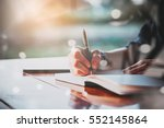 Stock photo people writing on notebook and work with calculator and laptop on wooden table 552145864