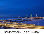 Saint-Petersburg, Russia - January 3, 2017: Aerial view of a highway with a cable-stayed bridge that crosses the frozen river winter night. - stock photo
