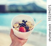 Small photo of Acai bowl food selfie picture. Closeup of healthy breakfast take-out on ocean background at hawaii beach. Berries and fresh fruits outdoors for a weight loss diet. Square crop for social media.