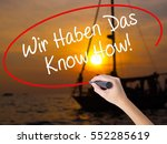 Small photo of Woman Hand Writing Wir Haben Das Know How! (We Have the Know-How in German) with a marker over transparent board. Isolated on Sunset Boat. Business concept. Stock Photo