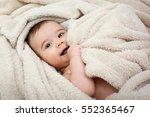 cute baby boy in bed under a... | Shutterstock . vector #552365467