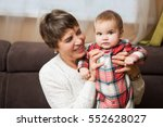 senior woman hold little baby... | Shutterstock . vector #552628027
