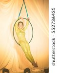 Small photo of Acrobatic artist sitting on the hoop, on stage