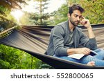man relaxing on hammock with... | Shutterstock . vector #552800065
