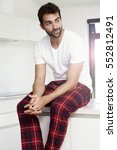 pajama dude sitting in kitchen | Shutterstock . vector #552812491