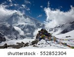 Colorful prayer flags on the French pass over mountain landscape. Huge snow-covered eightthousander Dhaulagiri mountain is on the background. Blue sky is covered with white clouds.