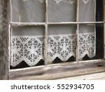 A Lace Curtain Adorns An Old...