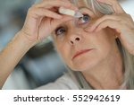 senior woman putting eye drop  | Shutterstock . vector #552942619