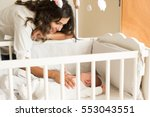 mother putting baby to sleep at ... | Shutterstock . vector #553043551