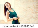 young happy woman measuring her ... | Shutterstock . vector #553049365