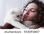 young lady kissing cat at home. ... | Shutterstock . vector #553093807