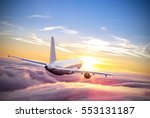 Commercial airplane flying above clouds in dramatic sunset light. Very high resolution of image - stock photo