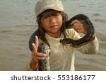 Small photo of SIAM REAP, CAMBODIA, 16 Jan 2008: Cambodian boy with the snake on the Tonle Sap Lake. The people in this district live in appalling conditions, in abject poverty...