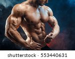 Unrecognizable Strong bald bodybuilder with six pack. Bodybuilder man with perfect abs, shoulders,biceps, triceps and chest, personal fitness trainer flexing his muscles in blue, red smoke