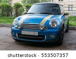A small blue car parked on the street. - stock photo