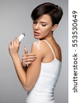 Small photo of Injury Treatment. Beautiful Woman Feeling Pain In Shoulders, Applying Medical Muscle Cream On Arm, Holding Cream Tube In Hand. Female Putting Lotion On Painful Shoulder. Health Care. High Resolution