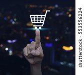Hand pressing shopping cart icon over blurred light city tower background, Shopp online concept