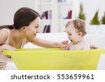 mother bathing her cute baby... | Shutterstock . vector #553659961