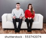 Stock photo shy woman and man sitting on sofa couch next each other first date pretty girl and handsome guy 553742074