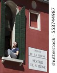 Small photo of Venice, Italy - 10 April 2016: young lady resting under the spring sun at her window. The historic city has a disproportionate share of older residents while young population is decreasing